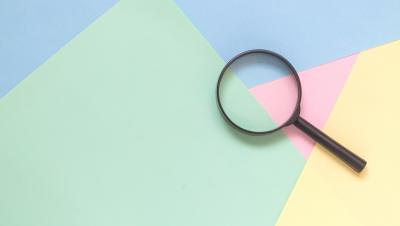 Magnifying glass on multi-coloured background